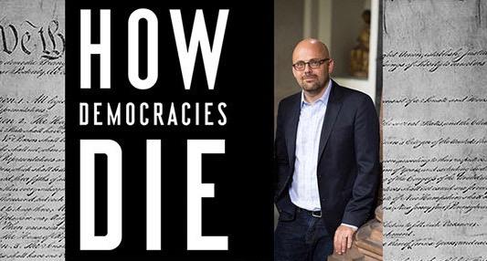 دانیل زیبلات در کنار پوستر روی جلد «دموکراسی ها چگونه می میرند»